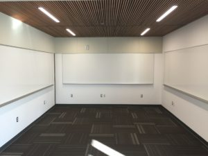 A completely empty office, with white boards on every wall.