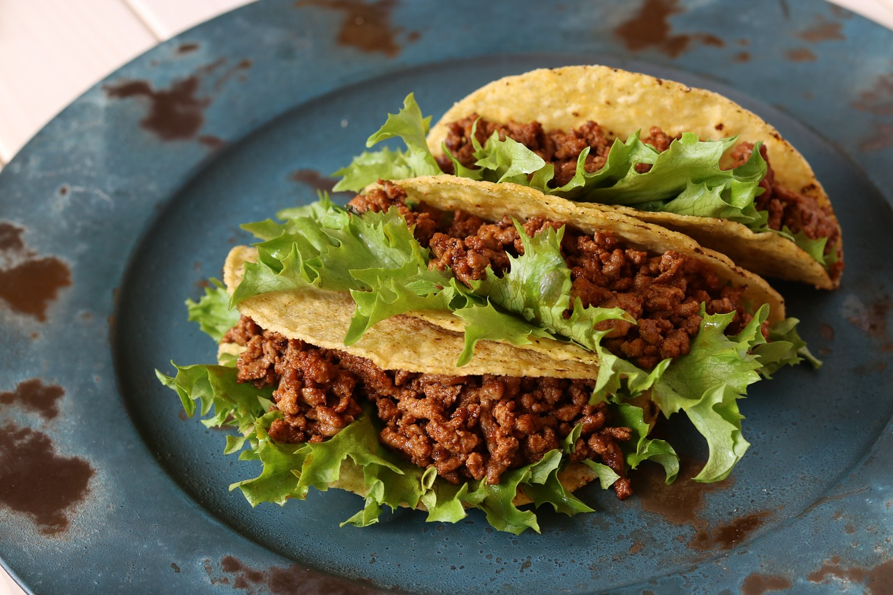 Three tacos in hard shells on a plate