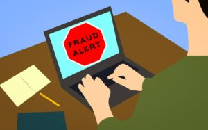 fraud alert sign on the laptop to help avoid office moving scams