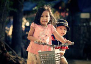 Kids driving bicycle in the neighborhood.