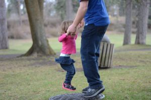 Girl and her father playing in the park.
