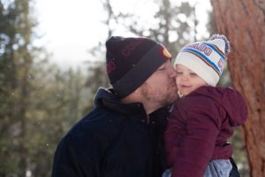 Father kissing his child wearing a Colorado beanie