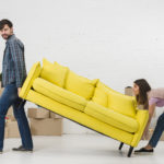 A man and woman moving a couch befre moving to Plantation, FL