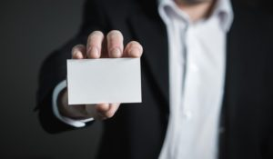 A man in a suit holding a card.
