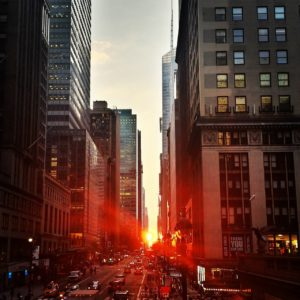 A picture of a Manhattan street as the Sun is setting down.
