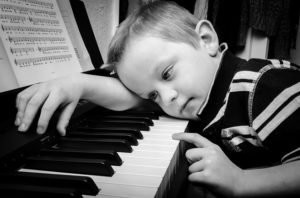 kid on a piano bored