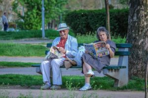 Two elderly people reading the newspapers on a bench.