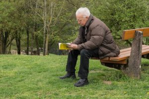 An elderly man reading a book in the park.