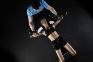Working out with a personal trainer, such as the girl on this picture, can help you stay fit after moving to Dubai.