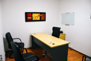 Small office with dark furniture.