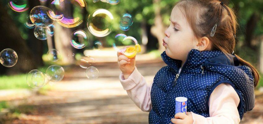 A little girl blowing bubbles.