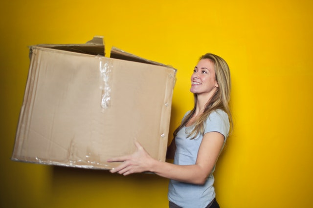 A lady with a box applying packing tips for busy moms.