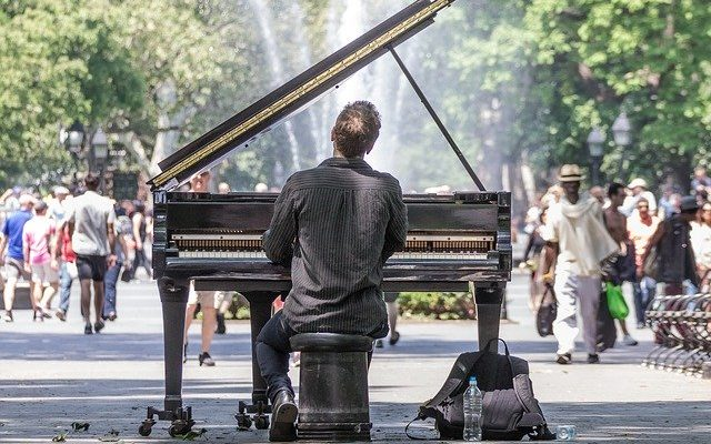 A man playing the piano in the street of Manhattan who has realized that moving from Sand Diego to NYC for a career in music is a good decision.