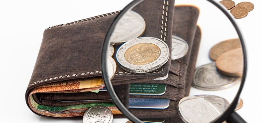A view of a wallet and some coins through a magnifying glass.