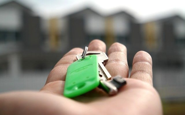 A person giving the keys to someone who's buying a house in San Diego.