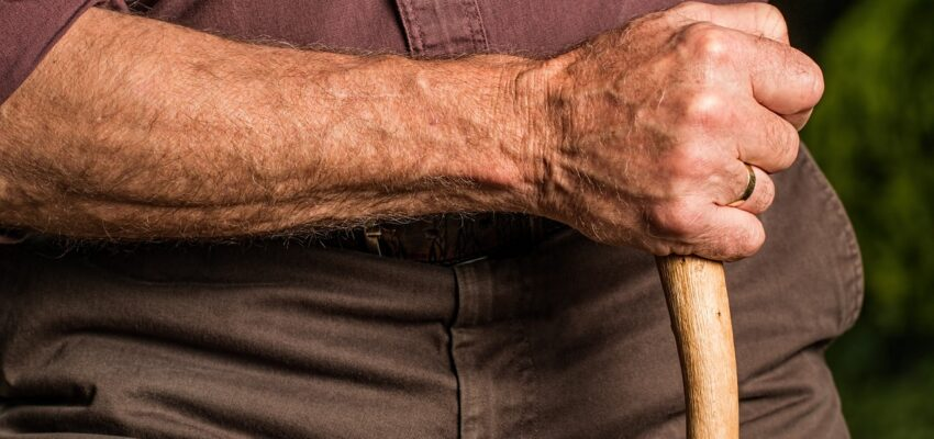 An elderly man holding s walking stick.