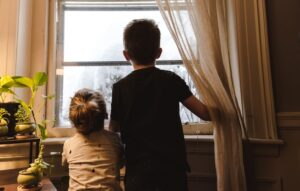 A boy and a little girl looking outside a window while their parents are online house hunting.