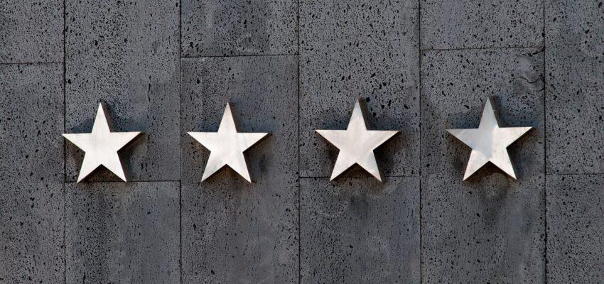 Four white stars on a dark background.