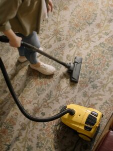 A person is cleaning the floor with a vacuum cleaner.