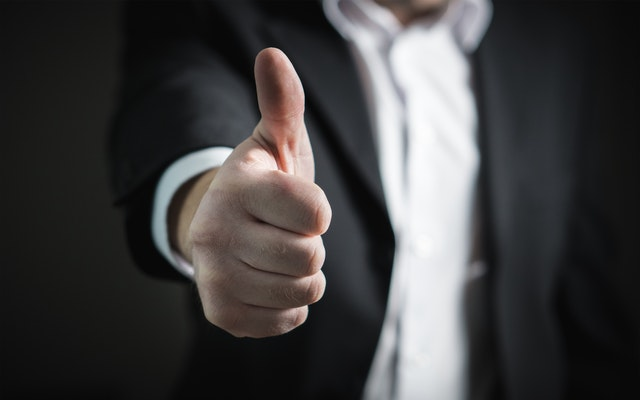 A man showing thumbs up approving an idea.
