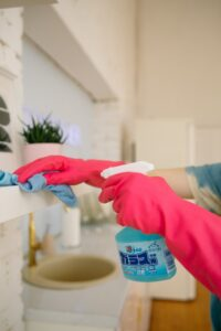 A person, wearing pink gloves, is cleaning the bathroom elements. Most people wonder about whether they should deep clean this part of their homes before or after they move in.