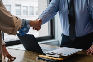 There are two people shaking hands after successfully negotiating a commercial lease for LA offices.