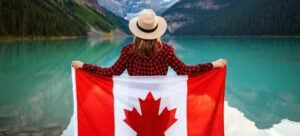A Woman wrapped in Canadian flag looking at lake