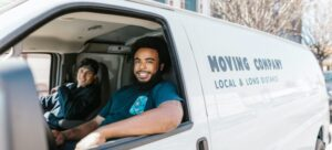 Two men in a moving company van who can assist you when moving from San Diego to Hamilton, Canada.