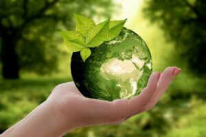 An illustration of a woman holding a green globe in her hand.