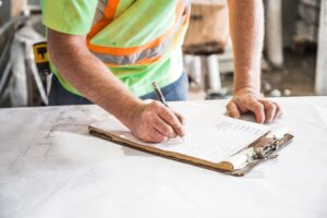 Contractor writing a thorough - one of the best benefits of hiring a contractor when renovating