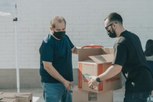 Men packing boxes as you will do once you realize all the reasons to expand your company to Texas
