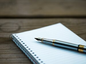 A pen on an open notebook. Before moving with your family from New Jersey to California it's of most importance you create a moving timeline.